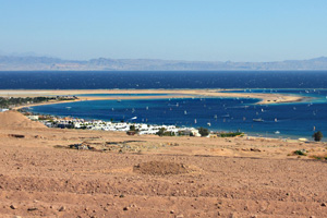 Golden sand beach and calm glistening waters of Dahab's crescent-shaped lagoon area, Egypt